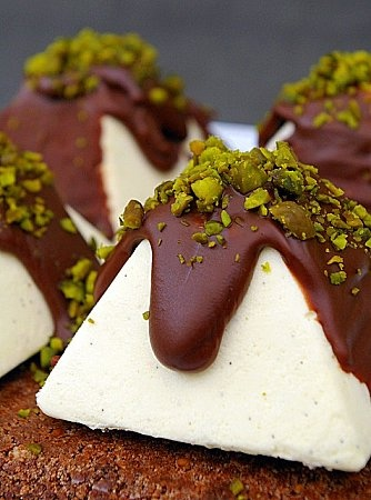 Pyramide de mascarpone au coeur de pistache-mascarpone mousse pyramids filled w pistachio mousse, topped w chocolate ganache and crushed pistachios then set on a buttery biscuit crust