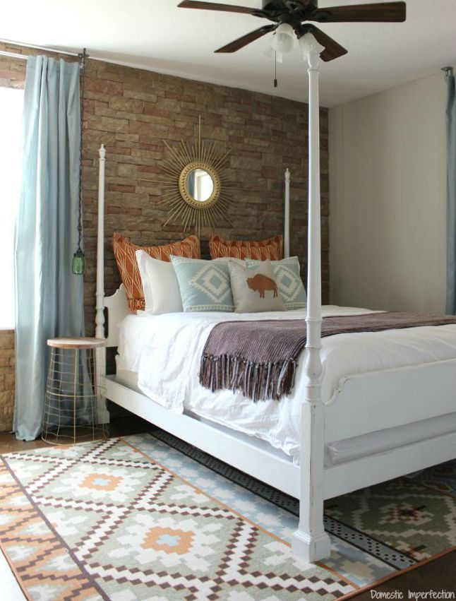 Southwestern bedroom makeover - so much better than the before! Love the rug, stone wall, and HUGE old map!