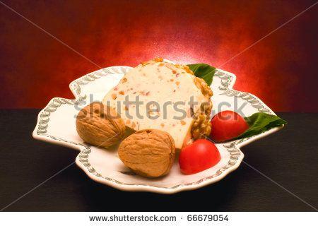 Italian Cuisine - Cheese - Piece of Italian Caciotta cheese seasoned with nuts.#foodphotos #stockphotos #healthyfood #foodingredients #ItalianFood #Shutterstock #bio #naturalfood #eatingwell #slowfood