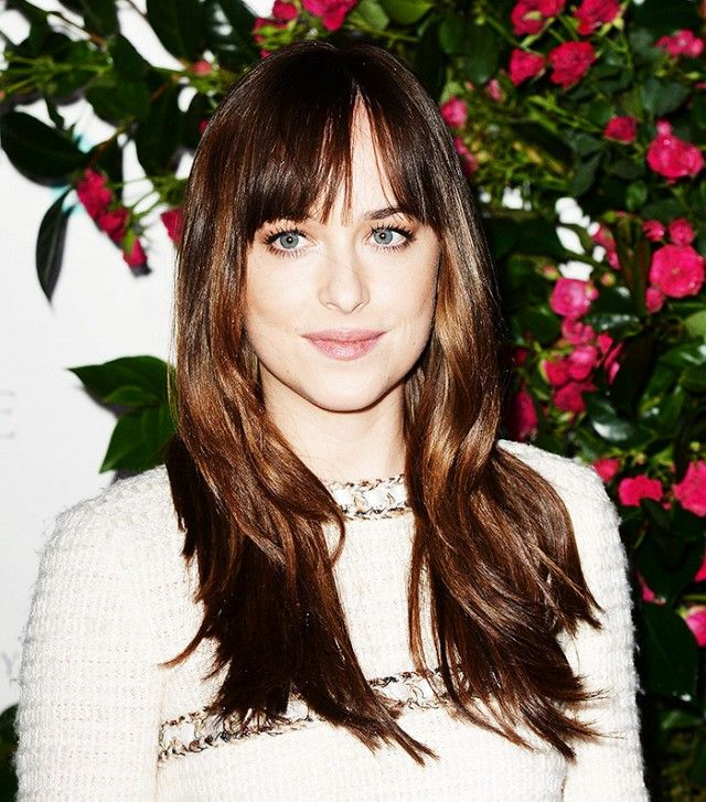 Dakota Johnson's version of the shag with bangs is tousled, choppy, and long with blunt bangs that part down the center