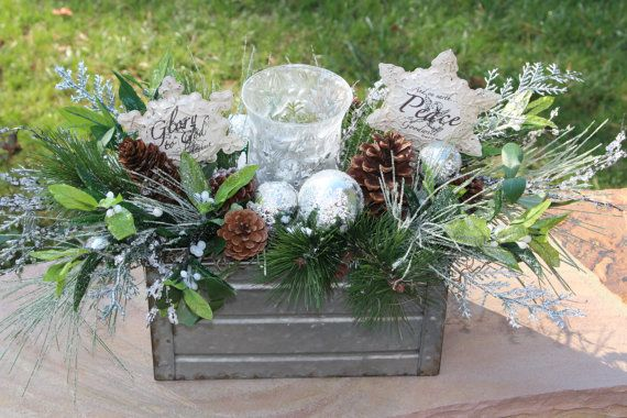 Beautiful and elegant Christmas Centerpiece that is sure to look amazing anywhere you decide to put it. This silver metal container is filled with different Christmas pine, pinecones, silver balls, holly with white berries, shimmery branches/leaves, a frosted hurricane candle holder with a glittery snowflake on the front and back as well as 2 snowflake shaped metal ornaments with  Glory to God in the Highest and  And on Earth Peace and Goodwill toward men on the other. Candle holder can fit…