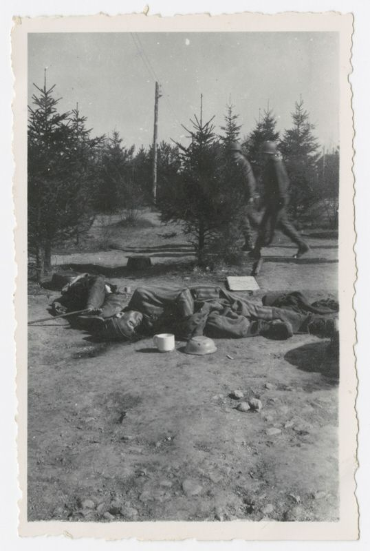 Two American soldiers lwalk by victims' corpses lying in an open field in the Ohrdruf concentration camp.  April 1945  World War Two