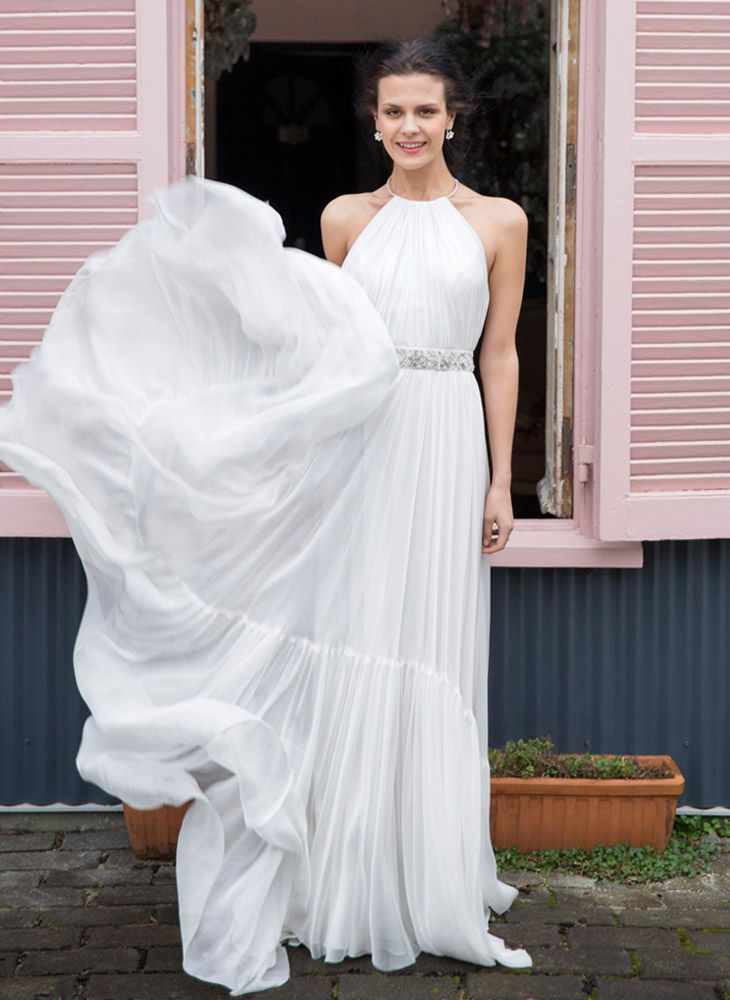 The allure of a bare back and a beautiful shoulder come together in this feminine free flowing halter neck wedding dress