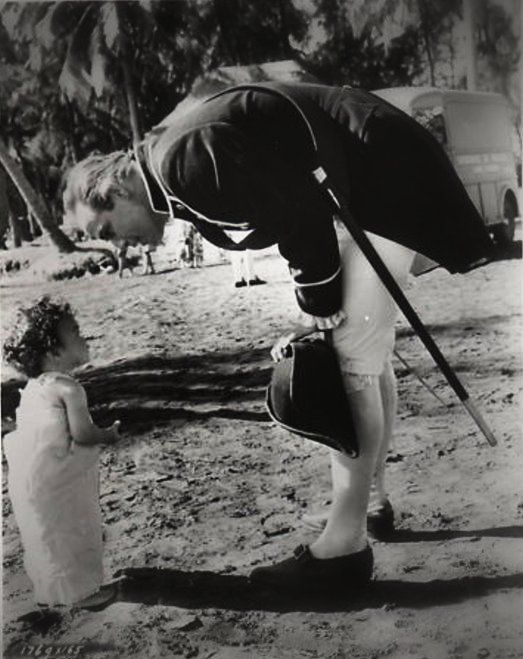 Marlon Brando talking to a little friend during the filming of Mutiny on the Bounty (1962)