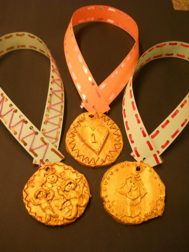 Klei medaille groep 3/4 olympische spelen. Na het bakken beschilderd met gouden plakkaatverf. Het lint is gemaakt van een stevig gekleurde strook die met de 23 ringband gaatjes maker even is voor geperforeerd. Kinderen rijgen de stroken met cadeaulint. Snelle leerlingen kunnen hem met wol nog mooier versieren