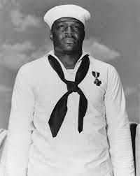 Pin honoring Pearl Harbor hero Dorie Miller. A black messman who was untrained in machine gun use due to rigid Naval segregation policies, Miller took over a machine gun aboard the USS West Virginia and was officially credited with downing two Japanese planes. Miller was honored as one of the first heroes of World War II, and six months after the attack was given the Navy Cross by Admiral Chester Nimitz.