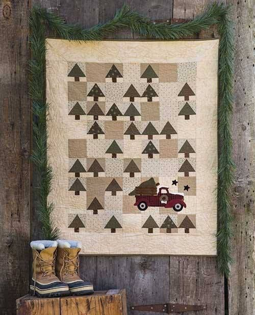 This holiday quilt is inspired by the family tradition of driving out to the country to cut down your Christmas tree. A patchwork of neutral fabrics serve as a backdrop for pieced trees in this complete Christmas quilt kit.