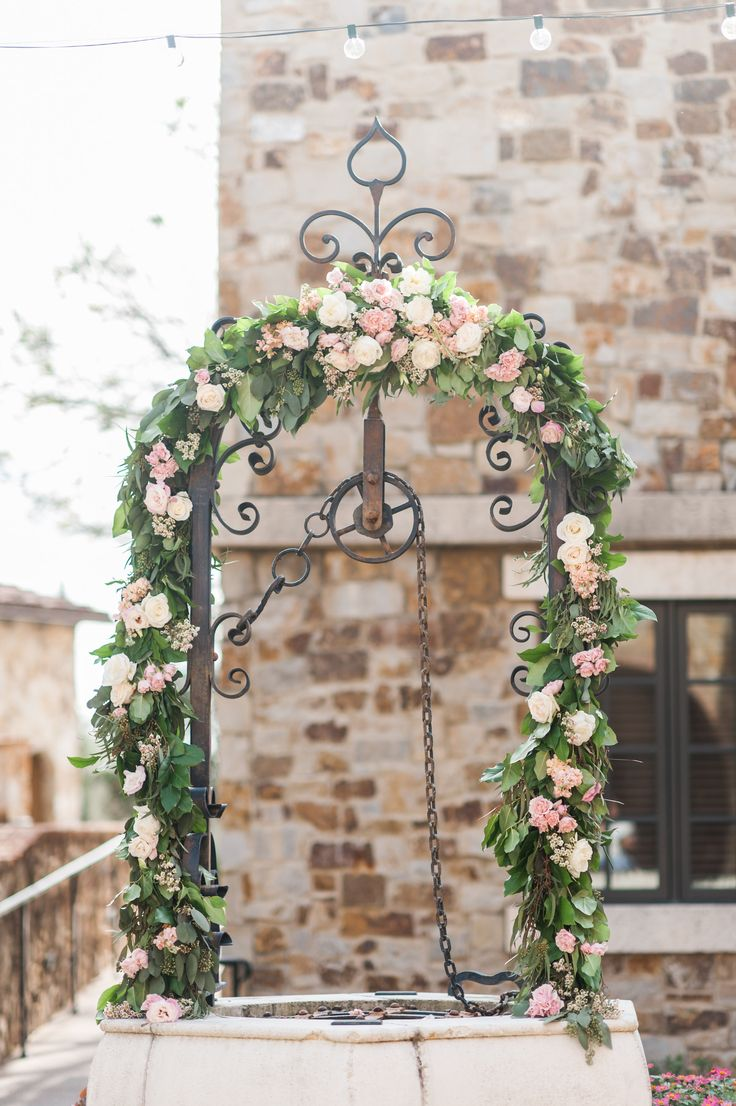 wedding ceremony at bella collina was set at the old well, the arch was  dressed with lemon leaf, seeded eucalyptus & olive garland garland filled with peach stock, vendela rose, white wax flower, light pink lisianthus & light pink majolik spray roses.