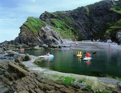 Ilfracombe Devon Tunnel Pools. tidal pool, sea pool, swimming pool, rock, people, children, boys, lifevests, canoes, paddles, oars, boating, girls, paddling, beach, shingle, families, adults, sea water, rocks, cliffs, sunny day