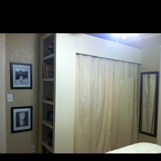 Our version of the DIY closet. Shelf turned outward + hanging rods + curtains = instantly quadrupled storage space.