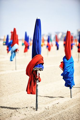 Parasol à la plage, Deauville, France. Beautiful beach. Love the colorful umbrellas all wrapped up.