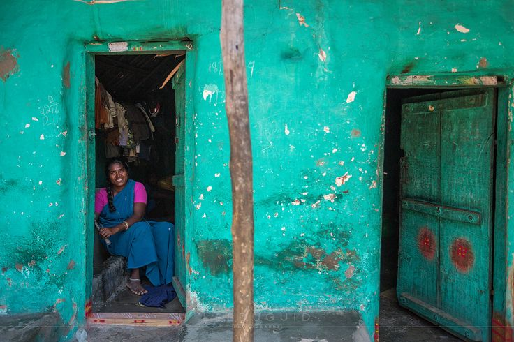 Lady cleaning pots in brightly coloured home in rural village on the outskirts of Mysuru, India.