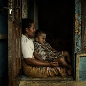 A mother sits with her infant child in a doorway in a hill village outside of Jakarta, Indonesia