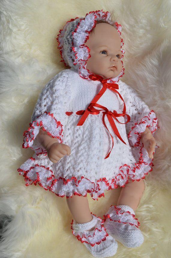 Un hermoso traje blanco adornado con cinta de raso y encaje. Para su bebé recién nacido o bebé reborn ver impresionantes en.  El vestido es en color blanco con una hermosa falda estampada y mangas largas. La línea del dobladillo y las mangas se recortan con el punto de encaje rojo y blanco. Cinta de raso roja se rosca a través de en la cintura para atar un moño al frente.  El capó tiene encaje rojo y blanco alrededor de la cara y en la corona. ATA bajo la barbilla con cinta de raso rojo…