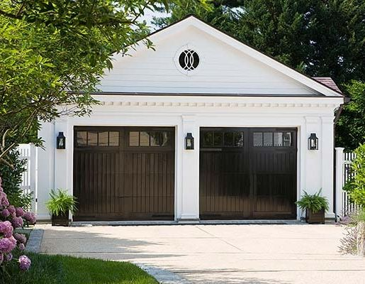 High-gloss black garage doors act like a mirrored surface for a home's driveway and surrounding greenery. Matching sconces reinforce the stark color and draw the eye up to the dentil molding.