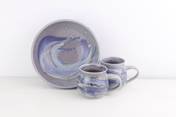 A great handmade pottery set for those peckish afternoons - 2 mugs for that hot cup of tea, chocolate or coffee - and a serving bowl for some marshmallows, biscuits or crisps. All 3 pieces have been hand thrown on a potters wheel, handglazed in a rustic palette in various ocean or sea coloured tones of blue, purple and teal / turquoise and all 3 are marked  Savill Pottery Canada.