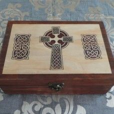Celtic Keepsake/Jewellery Box; Celtic Cross The knots, plait-work or weaving are a stunning feature of Celtic spiritual artwork. The weaving patterns represent the tribal migrations, spiritual devotion and travels through life. The Celtic cross usually has a circle around and a pure protective quality that wards of negative energies. Handmade and painted craft-wood box, made in Australia by Highland Handcrafts. $45.00au  Size: 28 x 19cm and 10cm deep