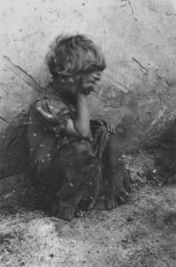 A Young Jewish girl with her hand obscuring her face sits outside in Deblin-Irena • Poland Ww2