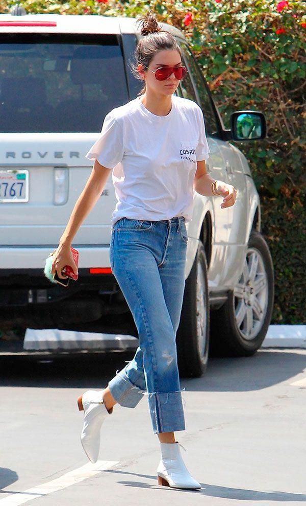 Street style look com camiseta, calça jeans e bota branca.