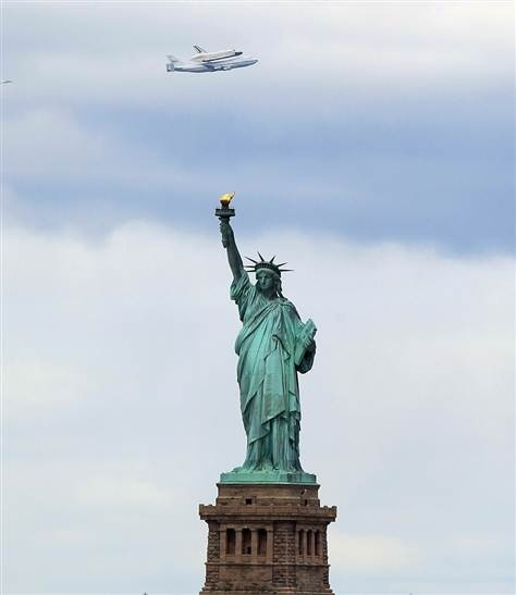 Riding atop a 747 shuttle carrier aircraft, the space shuttle Enterprise flies past the Statue of Liberty in New York Harbor on Friday.
