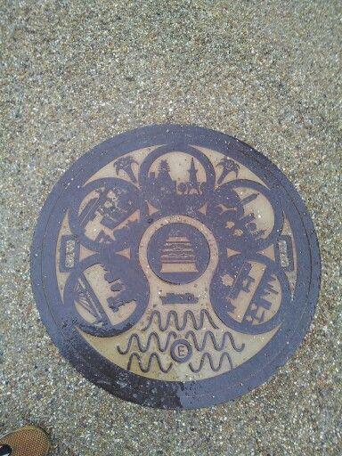 <愛知県名古屋市> 中央に市章(○に八) 八は鳩が2羽向かい合っている  周りに名古屋市の名所(名古屋港、宮の渡し、名古屋テレビ塔、東山動物園、名古屋国際会議場)を配置  それらの間に、市の花・ユリも描かれています。黄色蓋バージョン。 1989年に開催された名古屋デザイン博を記念したモチーフのマンホールです。