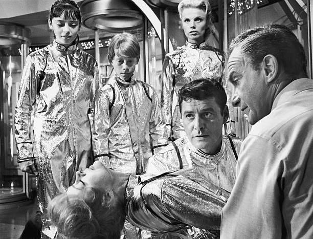June Lockhart lies on her back as Angela Cartwright Bill Mumy Marta Kristen Guy Williams and Jonathan Harris look on in a still from the television...