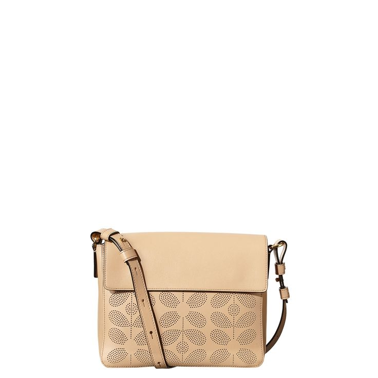 Orla Kiely: Sixties Stem punched leather unlined bag with magnetic flap to close. Adjustable long leather strap so that the bag can be worn across the body. Punched slip pocket and leather logo pocket detail on back. Gold coloured hardware. Inside details include slip pocket and elastic key chain.  Fawn colour has Black coloured coating and Pink colourway has a Gold coloured coating on inside of bag.    This product is made from high quality leather. This leather will develop a rich patina…
