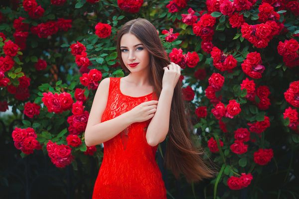 Girl wearing a red dress with red flowers background Stock Photo ...