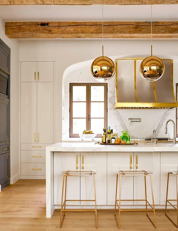 An arched doorway leads to a kitchen filled with a steel and brass French range hood lining a honed white marble cooktop backsplash as well as a steel and brass French stove.