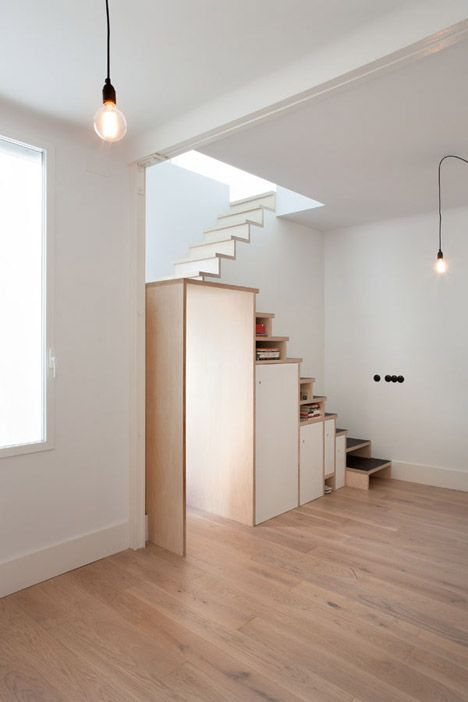 Plywood staircase by Buj+Colón Arquitectos integrates shelves and cupboards for a small flat.