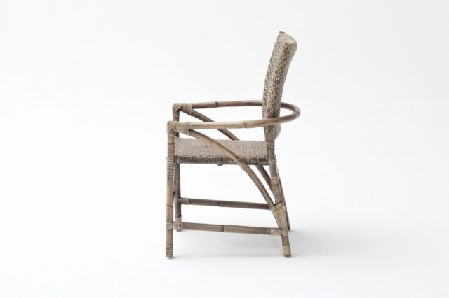 It's all about the weave of the Jester chair. The natural rattan is worked into mini arrow heads that come together to create a kind-of herringbone arrangement on the seat and open back. Surrounding it are thicker canes that bend and bow to form striking arms that slope downwards.