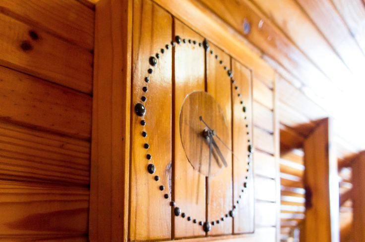 Clock made of pinewood complementing the wooden walls.