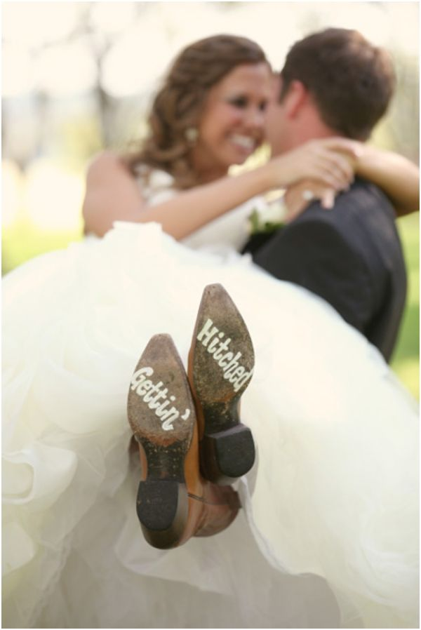 adorable bride and groom portraits, sweet bride and groom portraits, groom carrying his bride bridal style, the bridal style carry, cowboy boots with Gettin' Hitched painted across the bottoms, bridal footwear, bridal cowboy boots, rustic chic elegance wedding