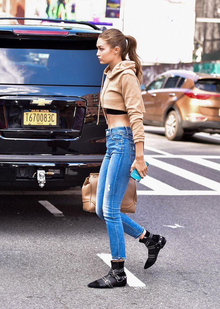 Gigi Hadid in skinny jeans, a cropped hoodie, and black booties.