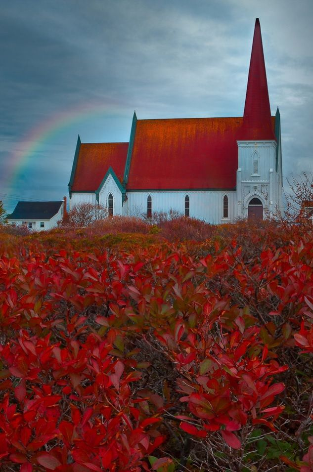 The Church at Peggy's Cove, Nova Scotia Canada. A stunning stunning rainbow crowns this striking red roofed church that stands majestically in a field of Crimson leafed foliage.