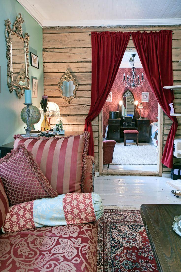 Kartanotyylisessä olohuoneessa on hirsiseinät ja samettiverhot. Mansion style livingroom with logwalls and velvet curtains. Turkoosiksi tuunattu 70-luvun nojatuoli. 70's armchair remade turquoise. | Unelmien Talo&Koti Toimittaja: Anette Nässling Kuva: Toni Härkönen