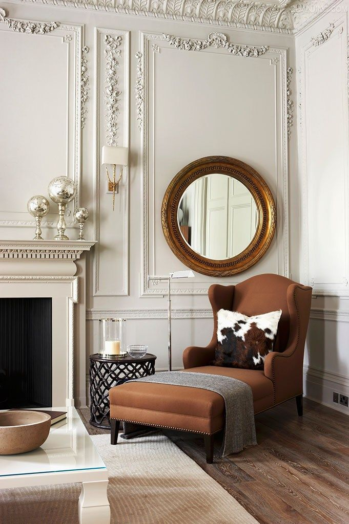 A large round gilt-framed mirror hangs above the brown upholstered wing-backed chaise : chaise house - Sectionals, Sofas & Couches