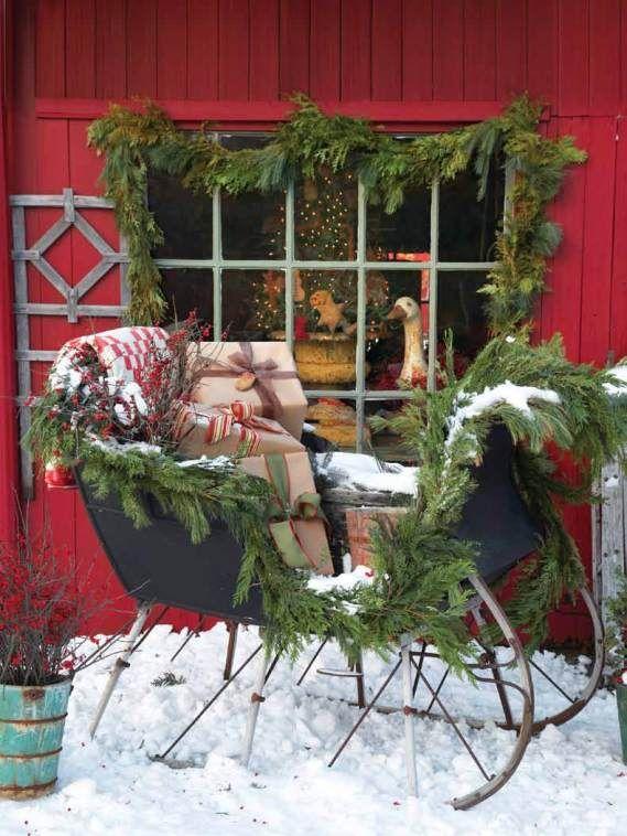 Decoración exterior con trineo, guirnalda de pino y muuuchos regalos.