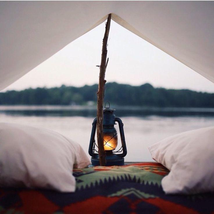 lit sous une tente avec lampe tempête et vue sur le lac