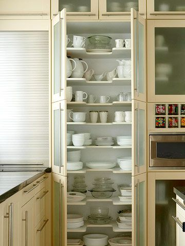 Maximize your kitchen's storage potential with floor-to-ceiling cabinets. Here a wall of cabinets with frosted-glass doors creates an open, modern look while concealing any bits of clutter. Inside the cabinets, each shelf has a U-shape cutout in the middle. The design makes it easy to see and reach both deep and shallow kitchen items.