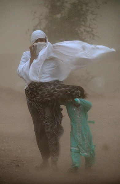 A woman and child struggle to walk in a dust storm, Islamabad, Pakistan.                               Photograph: Farooq Naeem/AFP (V)