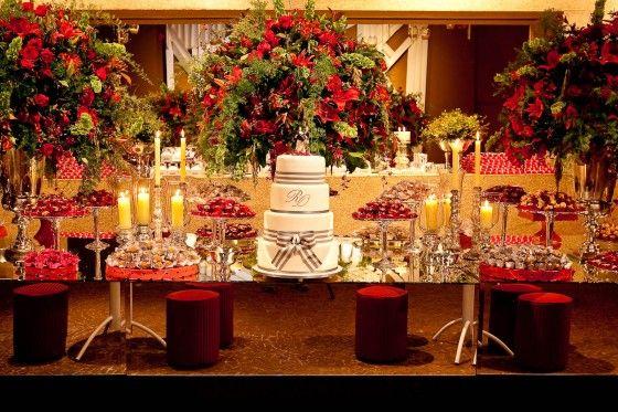 Decoração de casamento com velas, bolo branco e flores vermelha.