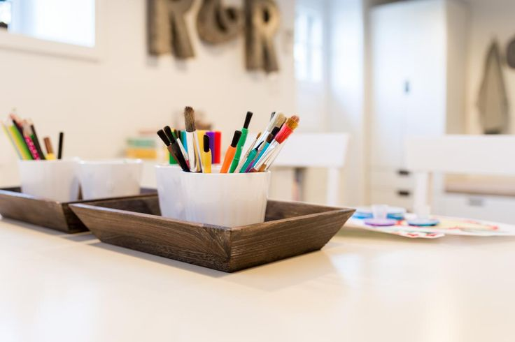 It's clearly a lively children's workspace. The kid's artwork—hung from Ikea picture rails and curtain rods with clips — fills the room with vibrant color. In this electronics-free zone, the kids paint, draw and play games at their white craft table.