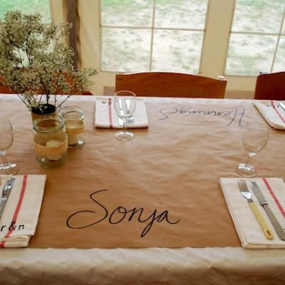 "Inexpensive, fun table idea. Use butcher paper (or brown mailing paper) as a ""tablecloth"". Write guests names at each place."