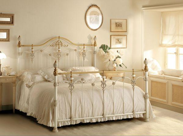 romántico dormitorio matrimonial con cama de hierro y bronce en blanco