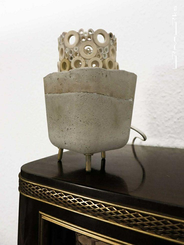 """Die Funzel """"dora"""" besteht aus einem massiven Betonkörper… Keramikbauteile aus der Isolierung eines Heizlüfters sind zylindrisch Angeordnet … selbige umschließen das Leuchtmittel … die drei Messingstifte … aus dem Stromanschluss des Heizlüfters … geben dem Lichtobjekt einen sicheren Stand …"""