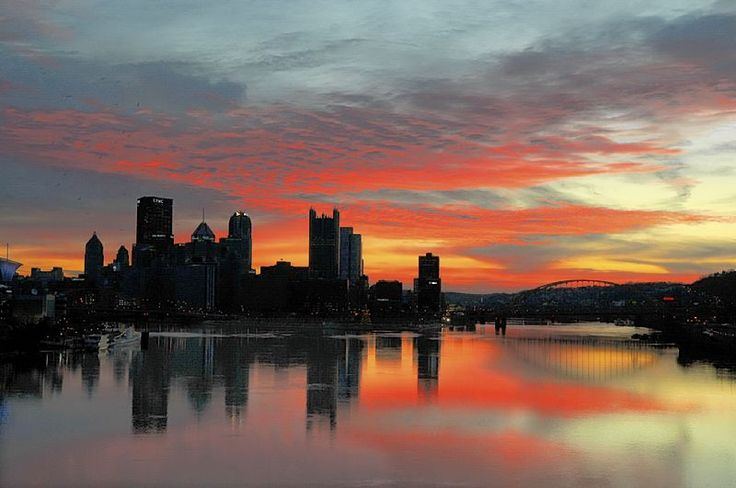 Clouds turn red over the Pittsburgh skyline, reflected in the Ohio River just before sunrise.