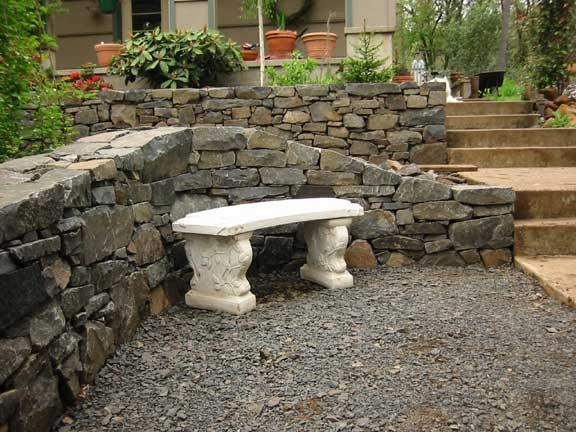 Close up of dry laid basalt retaining wall and bench.