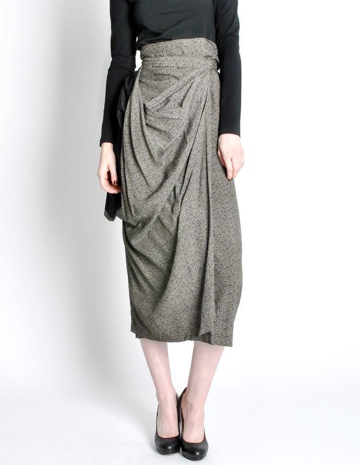 "When it comes to high, conceptual fashion, it doesn't get more top notch than this. This incredible vintage Comme des Garçons wrap skirt is to die for. It wraps and ties around the waist on the inside, as well as on the outside. This lightweight skirt has a great drape and side slouch that exposes the black lined fabric. Featuring a black and tan micro abstract pattern. Comme des Garçons Made in Japan 100% Rayon Recommended for a size Medium. Measurements: Waist 26-28"", Hip 36-38&quo..."