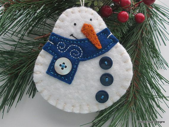 This happy snowman ornament is made of snow white wool felt. The scarf is hand cut from a dark blue wool felt and decorated with a large ivory colored button and freehand stitching. The carrot nose is wool felt too. This snowman sports three deep blue buttons down his belly. On the back I have stitched one of my Woolly Bug Designs labels and added three little blue star shaped buttons. Enjoy !  The size of this snowman ornament is 3 1/2 tall and 3 1/4 inches wide at the widest place. The…